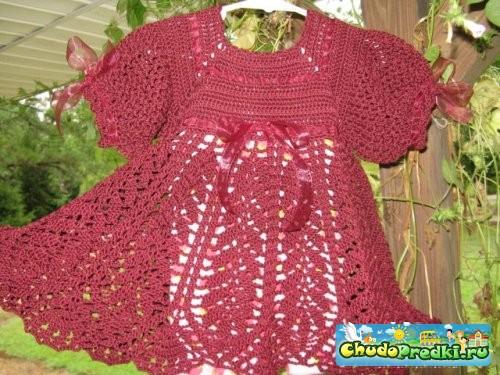 Оригинальное детское вязаное платье украшено ленточками, которые продеваются.